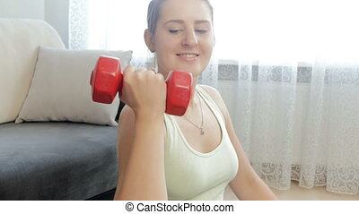 Closeup 4k video of young woman exercising in living room with dumbbells
