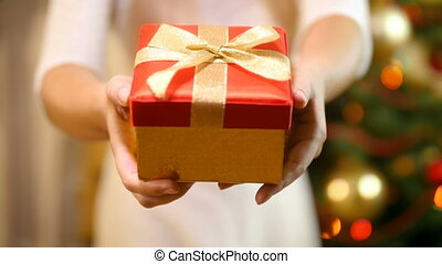 Closeup 4k video of young woman holding Christmas gift and showing it in camera