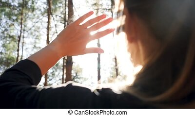 Closeup 4k video of young woman looking on bright sun through her fingers in the forest