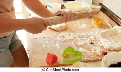 Closeup 4k video of young woman preparing rolling pin and rolling dough for pie on wooden countertop