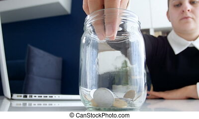 Closeup 4k video of young woman sitting in office and throwing metal coins in glass jar