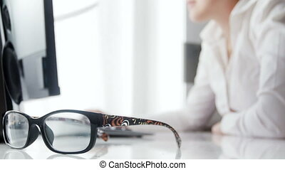 Closeup 4k video of young woman working in office. Focus on eyeglasses lying on office desk