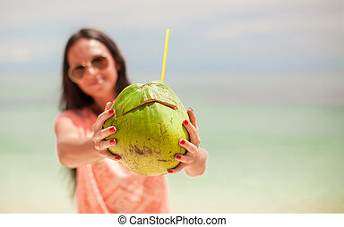 Closeup a coconut in hands of young happy girl