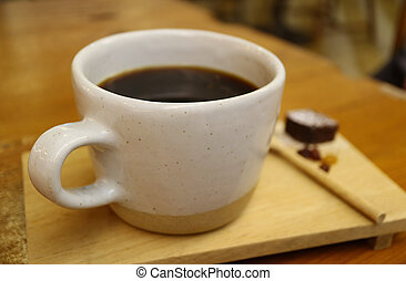 Closeup a cup of Hot black coffee served on wooden tray