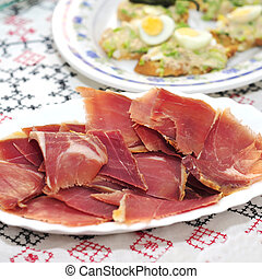 spanish serrano ham - closeup a plate with spanish serrano...