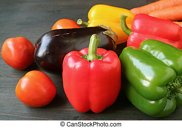 Closeup a red bell pepper with other colorful vegetables on wooden table
