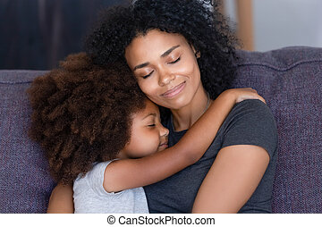 Closeup african daughter embracing mother sitting on couch at home
