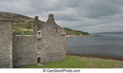 Closeup of ancient castle ruins at sea bay aerial. Nobody nature seascape with boats. Historic heritage of Hamilton dynasty palace on ocean coast of Arran Island, Scotland, UK, Europe. Drone shot
