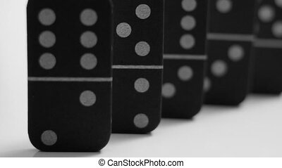 Closeup and pan of black dominoes isolated on white - A...