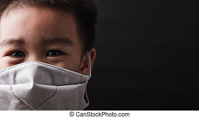 Asian little child wearing protective face mask with fear in the eye, prevent germs
