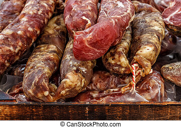 Closeup, assorted different kinds of meat: salami, sausages, smoked meat.