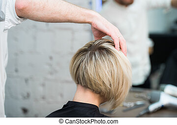 Closeup back view of teen young girl woman sitting in chair in hair salon looking in mirror while hairdresser checking her new haircut