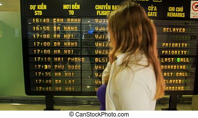 Closeup Backside Blond Girl Looks at Timetable in Airport -...