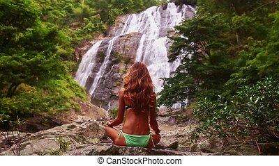 Closeup Backside Girl in Swimsuit in Yoga Pose by Waterfall