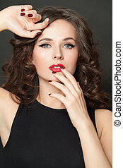 Closeup beauty portrait of beautiful fashion woman brunette with makeup, curly hair and red manicured nails