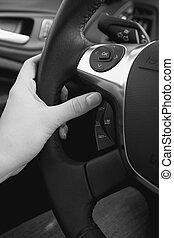 Closeup black and white photo of female driver adjusting cruise control system on steering wheel