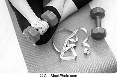 Closeup black and white photo of young woman sitting on fitness mat and lifting dumbbells
