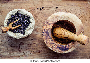 Closeup black pepper in wooden bowl with mortar and pestle...
