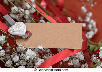 Closeup blank card for message surrounded by flowers and red ribbon