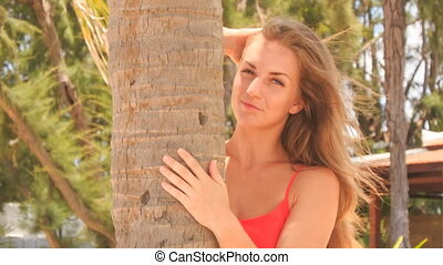 closeup blond girl in red hides behind palm smooths hair