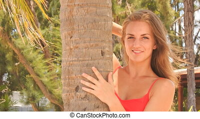 closeup blond girl in red looks out of palm smooths hair