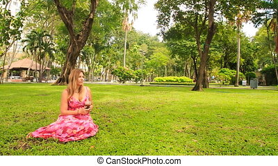 Closeup Blond Girl in Red Sits on Lawn Drinks Juice with Straw