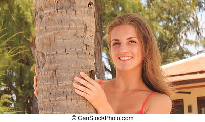 closeup blond girl in red tries hide behind palm trunk smiles