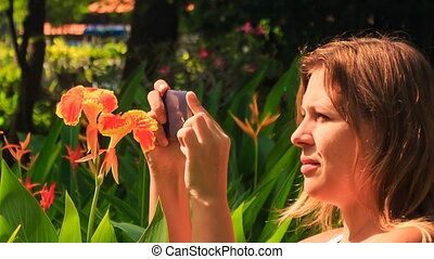 Closeup Blond Girl Takes Photo of Tropical Flower in Park