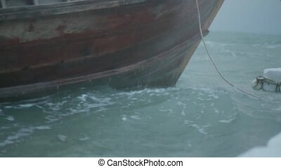 Closeup boat bow in restless sea over cloudy dark sky -...