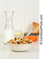 closeup bowl of granola raisin almond cereal with a spoon
