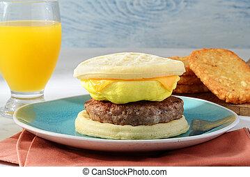 closeup breakfast sausage egg waffles sandwich with orange juice
