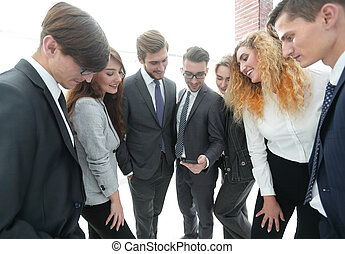 business team looking at a smartphone screen.