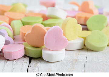 Closeup of a group of pastel candy Valentine's hearts on a rustic white wood table. Horizontal format.