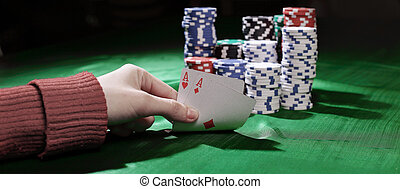 closeup. casino chips and playing cards in the player's hand.