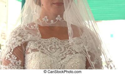 Closeup Caucasian Bride in White Lacy Dress under Veil
