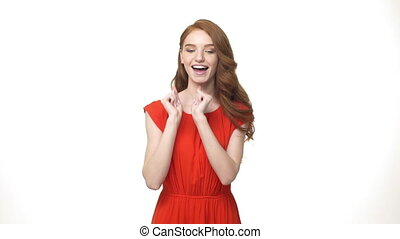 Closeup caucasian young women portrait in orange dress shy dancing over isolated white background