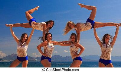 closeup cheerleaders demonstrate stunt Swedish falls on beach