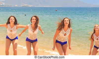 closeup cheerleaders in uniform jump lift hands in shallow water