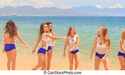 closeup cheerleaders jump gambol wave hands in shallow water