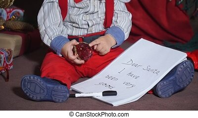 Closeup, child sitting under the tree with a letter to santa