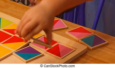 closeup child's hands compose wooden puzzle on table -...