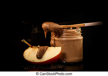 closeup chocolate peanut butter in glass jar with slice of apple