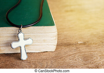 Closeup christian cross and bible on old wooden table with sunlight.