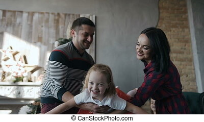 Closeup. Christmas day and happy family. Small girl being glad to spend holidays with her mother and father. Little girl flying on hands in his parents looking at the camera