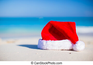 Closeup christmas hat on a white sandy beach