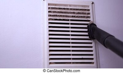 Closeup Cleaning Ventilation Grill from Dust with Vacuum...
