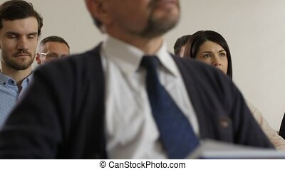 Closeup audience of marketing department employees sitting in conference hall during corporate business training. Group of colleagues attentively listening to own director presenting new work strategy