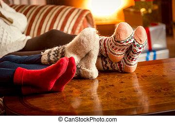 Closeup conceptual shot of family warming feet at fireplace