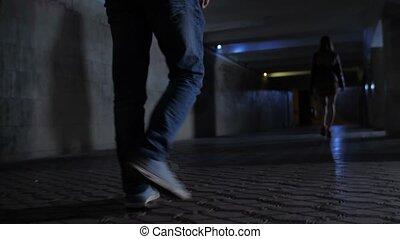 Closeup criminal's legs chasing victim in darkness -...