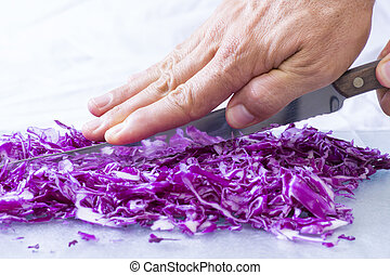 Closeup cutting red cabbage - Closeup of hand pressing spine...